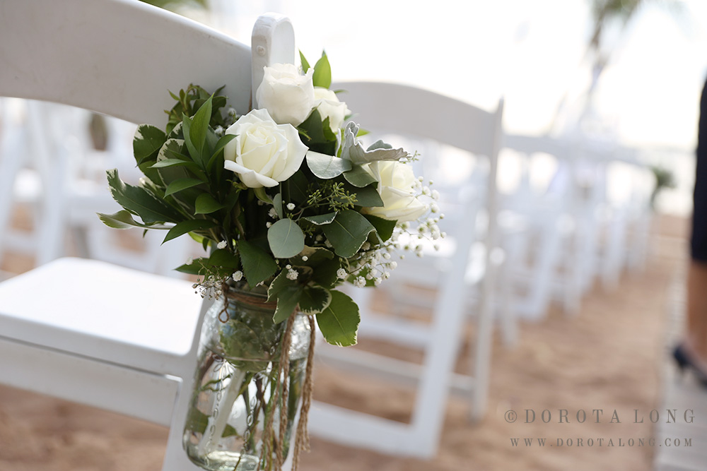 flower bouquet attached to rows of white chairs during wedding ceremony