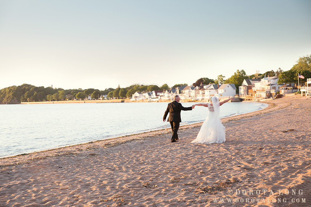 bride and groom walking on the beach with hands in the air, happy during sunset