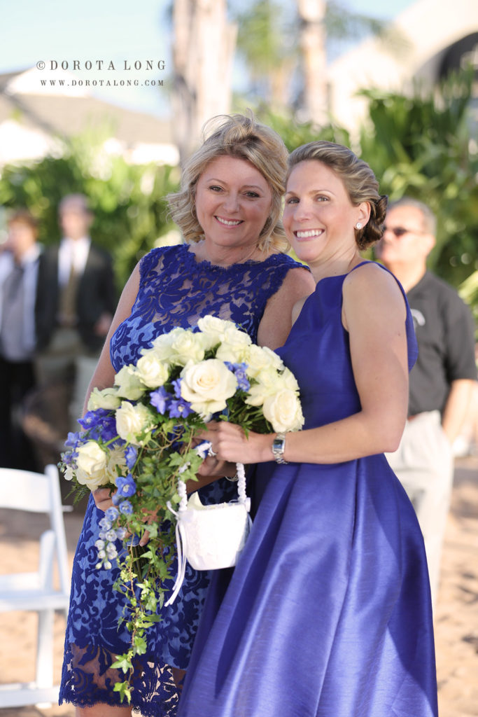 two bride maids wearing blue smiling and looking right at the camera during outdoor wedding ceremony in connecticut