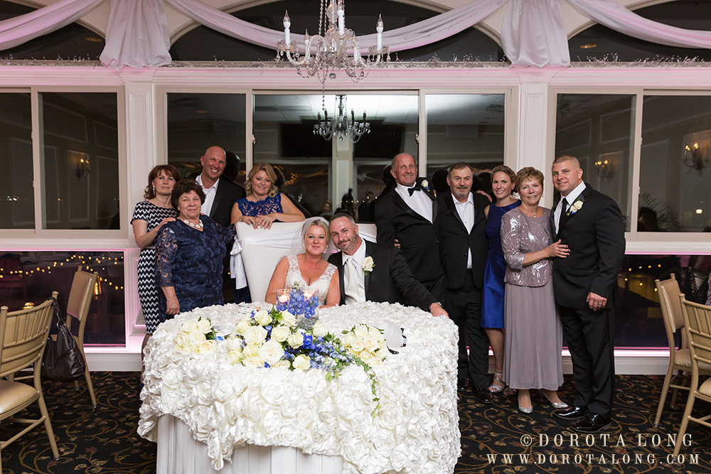 the family of the bride gathered around the table everyone looking right at the camera and wedding photographer