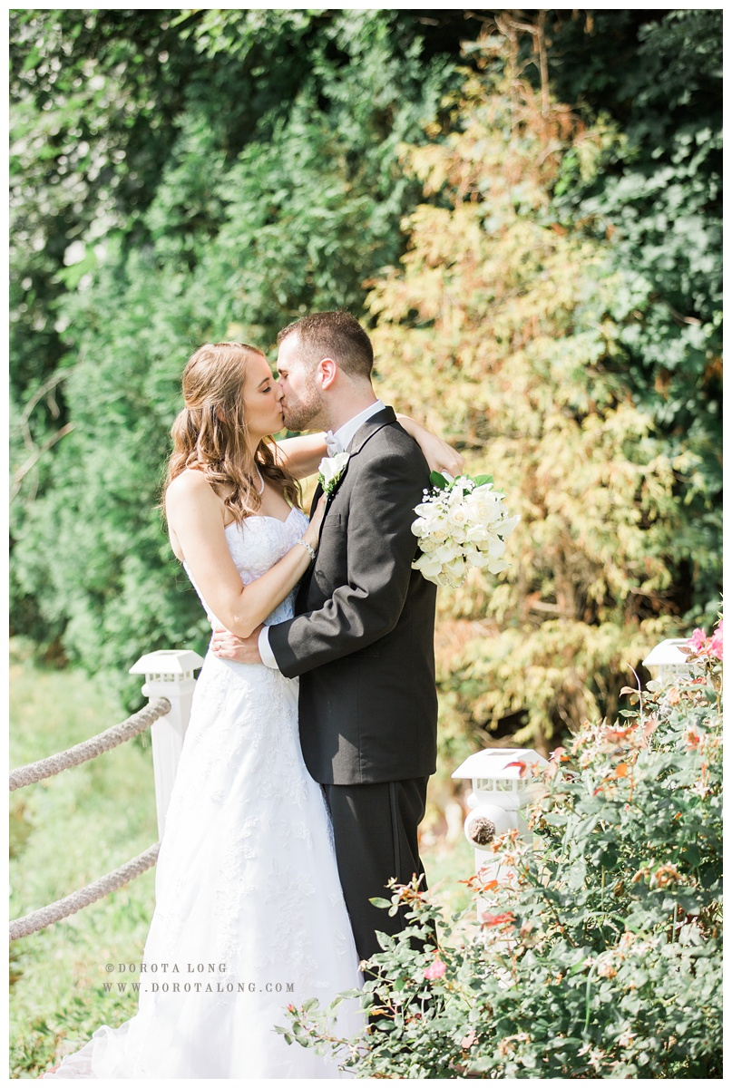 Villa Bianca Seymour wedding photographed by Dorota Long. A couple is kissing outside the venue near the pond